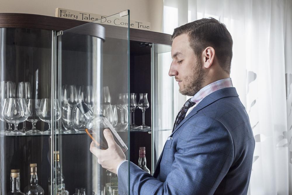 Tomasz Miler z butelką whisky