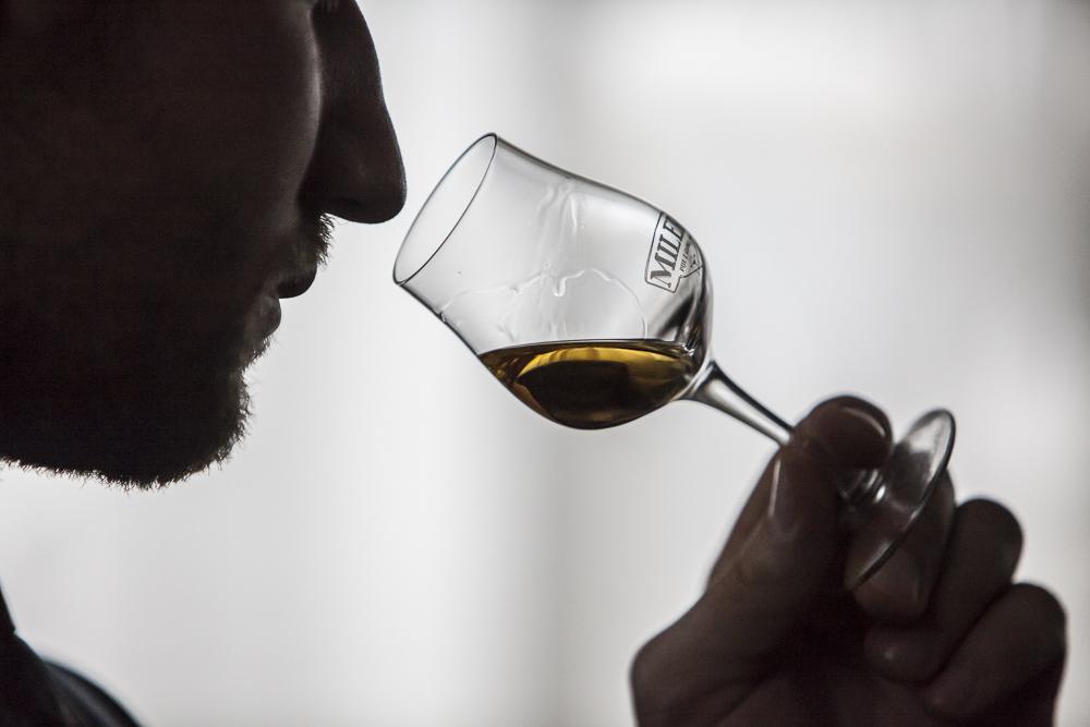 Tomasz Miler zbliża nos do kieliszka z whisky