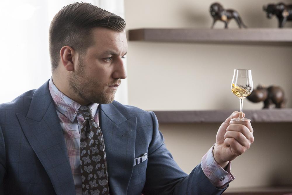 Tomasz Miler przypatruje się whisky w kieliszku